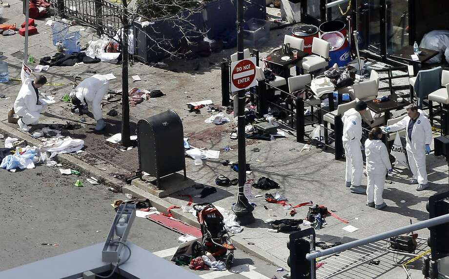 Investigators examine the scene of the bombing near the finish line of the 2013 Boston Marathon, a day after two blasts killed three and injured 260. Photo: Elise Amendola, Associated Press