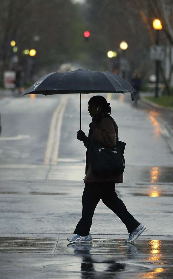 Umbrellas were put into use as rain fell in Sacramento, Calif., Wednesday, March 11, 2015. A storm brought rain to parts of Northern California and some snow to the upper elevations of the Sierra Nevada. Photo: Rich Pedroncelli, Associated Press