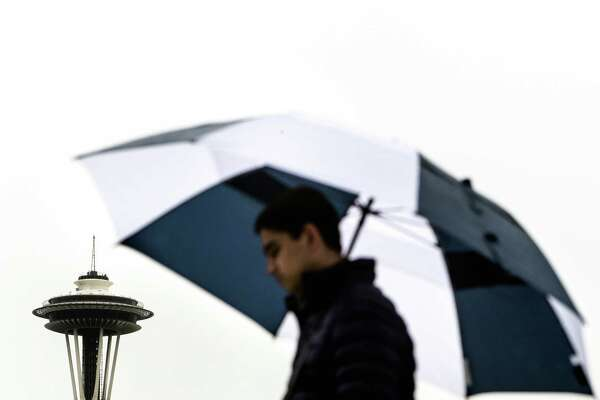 OceanGate intern Om Chatterji, 19, keep rain off of him with a umbrella Wednesday, March 11, 2015, at MOHAI in Seattle, Washington.