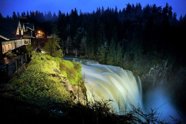 As shown in a long exposure photograph, a bloated Snoqualmie Falls dumps water down the river Monday, January 5, 2015, in Snoqualmie, Washington.