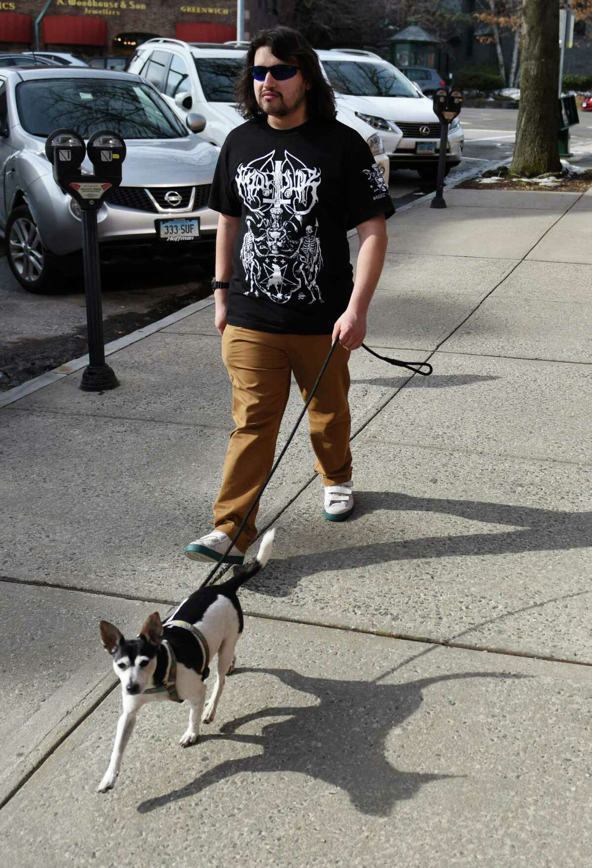 Bertie Connally, of Greenwich, wears a T-shirt while walking his rat terrier, Sonny, down Greenwich Avenue in downtown Greenwich, Conn. Wednesday, March 11, 2015. Wednesday's weather was a relative heat wave with temperatures rising into the mid-50s. Temperatures for the rest of the week andd into the weekend are expected to be in the mid-40s.