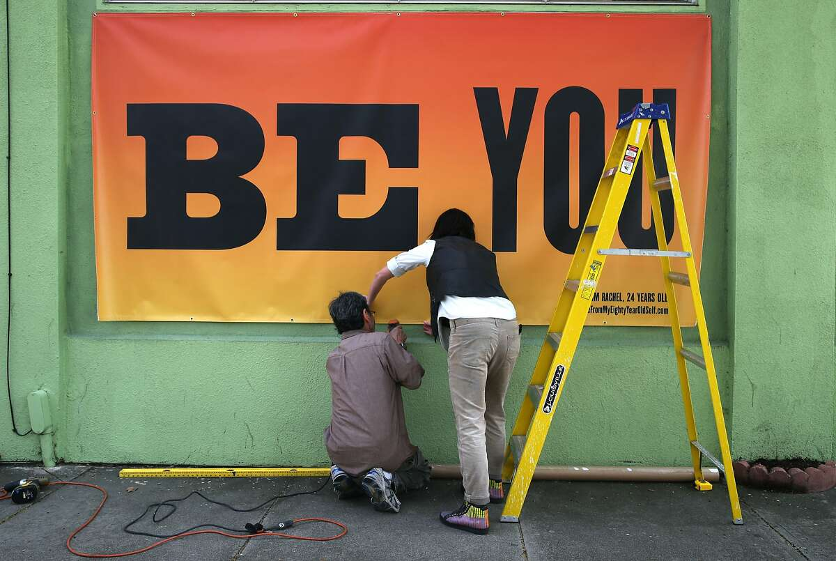 """Kala Art exhibit curator Amanda Curreri (right) installs an art project created by artist Susan O'Malley on a San Pablo Avenue business in Berkeley, Calif. on Wednesday, March 11, 2015. O'Malley died tragically a week before she was due to deliver twin girls. Her art project, """"Advice From My 80-year-old Self"""" is part of an exhibition at the Kala Art Institute in Berkeley opening May 7."""