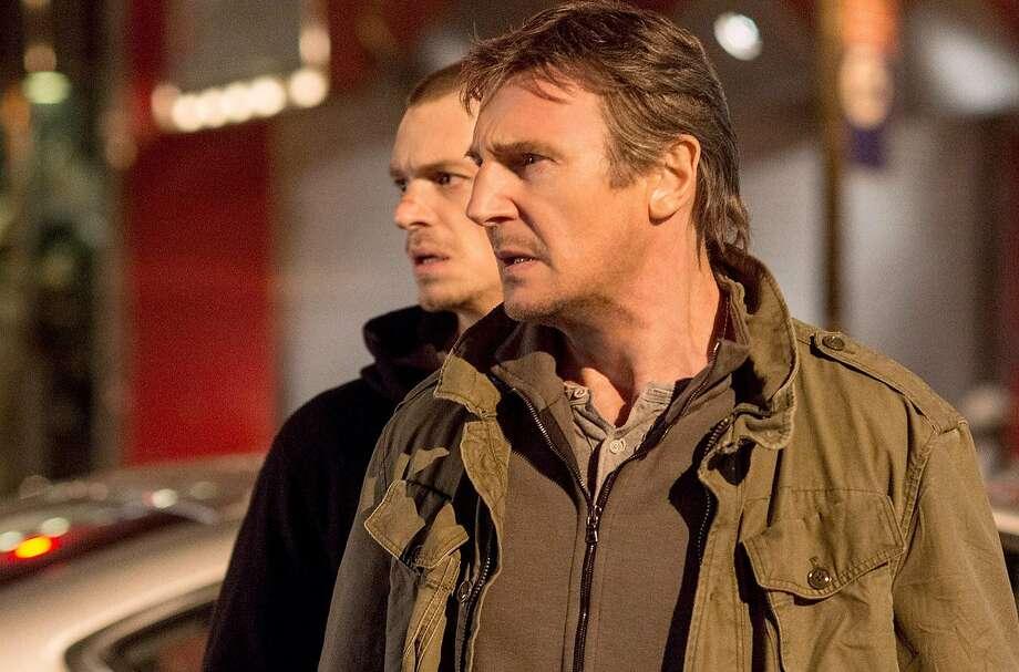 "Ex-hit man Jimmy (Liam Neeson, front) gears up to aid son Michael (Joel Kinnaman) in ""Run All Night."" Photo: Handout, Washington Post"