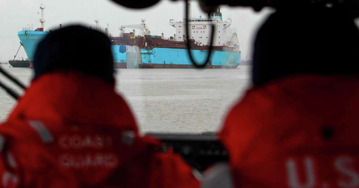 Members of the United States Coast Guard view the damaged hull of the Carla Maersk a chemical tanker Wednesday March 11, 2015 in the Houston Ship Channel. The Carla Maersk and the Conti Peridot, a Liberian bulk carrier collided Monday March 9, 2015 in the Houston Ship Channel. The Carla Maersk was carrying 216,000 barrels of gasoline additive which began to spill into the water after the collision.