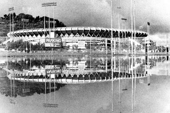 Top: Candlestick Park is reflected in Lake Candlestick — its flooded parking lot — in a rare scene captured in December 1981. Above: Frank (left) and Edward DiProsper watch the 2014 National League Championship Series from the upper deck at AT&T Park.