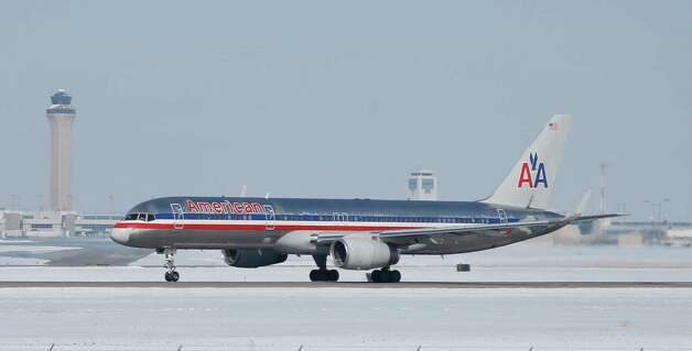 An American Airlines jetliner follows the ribbon of runway to take off from snow-covered Denver International Airport Monday, Feb. 23, 2015, in Denver. A winter storm that lingered through the weekend finally moved out of Colorado and into the southern Plains states Monday, sending temperatures plunging in the region while glazing roads with a covering of ice to make travel treacherous for residents weary of the winter. (AP Photo/David Zalubowski) ORG XMIT: CODZ101 Photo: David Zalubowski / AP