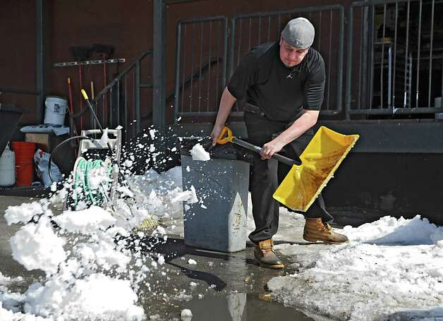 Maestro's employee Josh Coe breaks up snowbanks and throws the snow on the pavement to melt in the warm sun behind the restaurant on Wednesday, March 11, 2015, in Saratoga Springs, N.Y. (Lori Van Buren / Times Union) Photo: Lori Van Buren