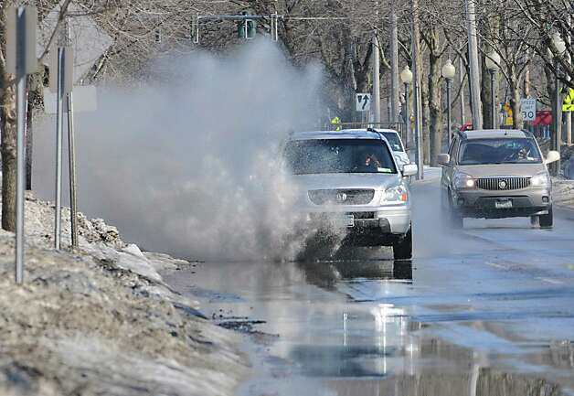 Cars splash in the puddles along Union Ave. on Wednesday, March 11, 2015, in Saratoga Springs, N.Y. Roadside puddles are abundant after a recent spurt of warm weather. (Lori Van Buren / Times Union) Photo: Lori Van Buren