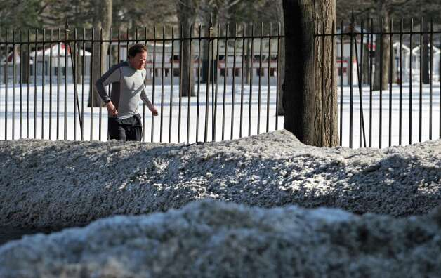 A jogger is seen running behind some dirty snowbanks along Union Ave.  Wednesday, March 11, 2015, during a day of temperate weather in Saratoga Springs, N.Y.  (Lori Van Buren / Times Union) Photo: Lori Van Buren