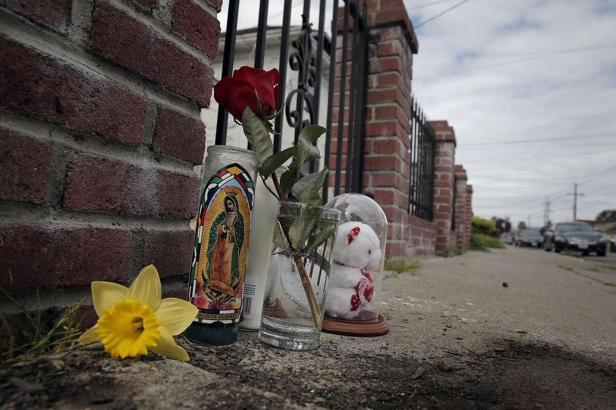 A small memorial lies on Chestnut Street in Oakland, Calif, on Wednesday, March 11, 2015, where Chyemil Pierce was shot and killed trying to protect her children on Tuesday. The young mother managed to shoo away her kids before a stray bullet from a gunfight up the street hit her.