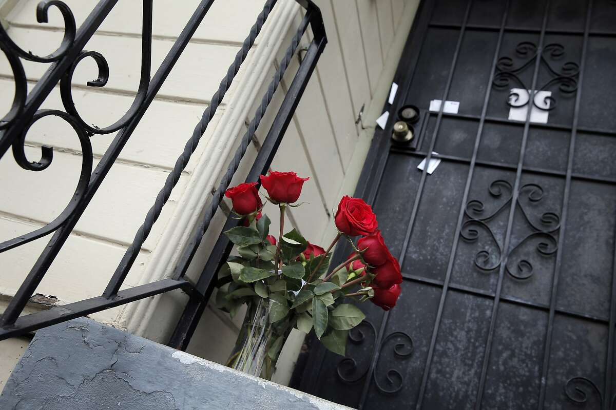 A bouquet of roses sits on the porch of Chyemil Pierce's home on Chestnut Street in Oakland, Calif, on Wednesday, March 11, 2015, where Pierce was shot and killed trying to protect her children on Tuesday.