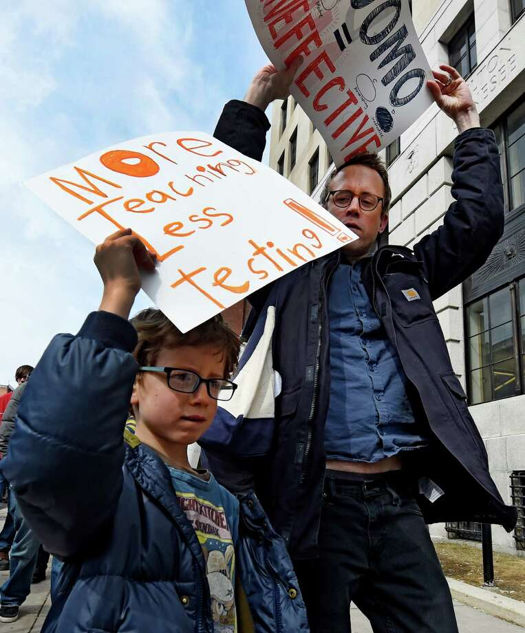 Gus Pauly, 7, marches with his father Ted Pauly of Brooklyn as they join a large group of people marching in the Parade for Public Education Wednesday afternoon, March 11, 2015, in Albany, N.Y. The demonstrators were showing their solidarity against Governor Cuomo's budget figures for public School.   (Skip Dickstein/Times Union) Photo: SKIP DICKSTEIN / 00030943A