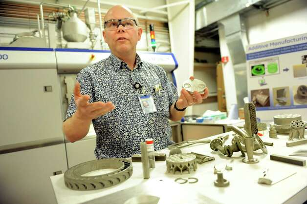 Material scientist John Deaton shows parts made on a direct metal laser melting machine, which is behind him, on Wednesday, March 11, 2015, at GE Global Research on Niskayuna, N.Y. (Cindy Schultz / Times Union) Photo: Cindy Schultz / 00030972A