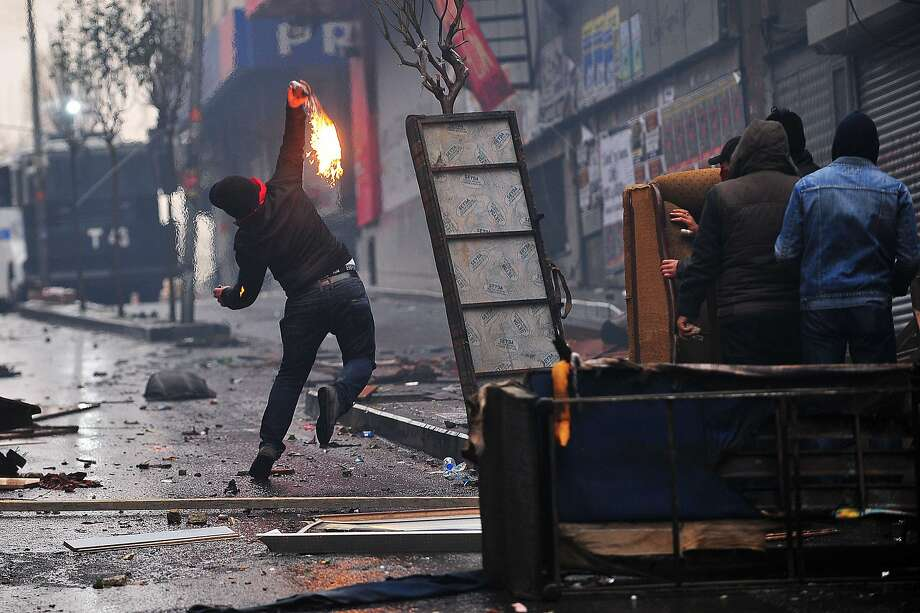 A man throws a molotov cocktail at riot police, on March 11, 2015 in Istanbul, during clashes  following a protest in memory of a teenager killed in 2013 anti-government demonstrations and whose death has become a rallying cause for opponents of President. Photo: Ozan Kose, AFP / Getty Images