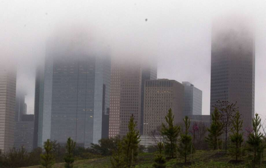 Executives at some Houston companies sound pessimistic in a new survey. Above, low-lying clouds cover the downtown skyline on Thursday, March 12, 2015. Photo: J. Patric Schneider, For The Chronicle