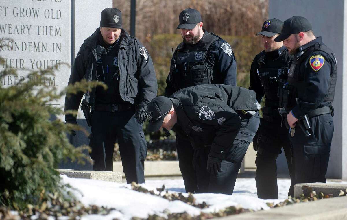 Stamford police officers search Veteran's Park in Stamford, Conn., on Thursday, March 12, 2015, after Antonio Muralles was murdered after he was stabbed, beaten and robbed Wednesday night.