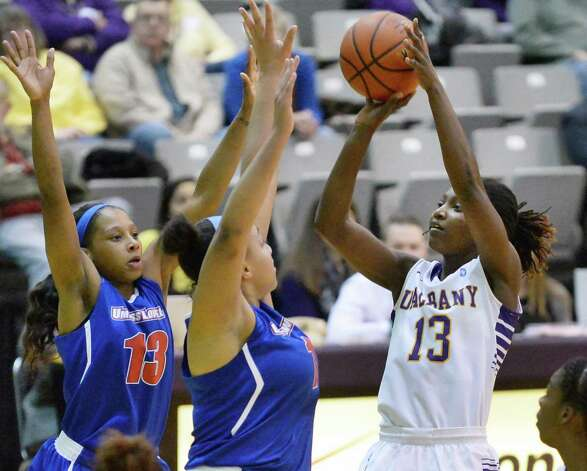 UAlbany's #13 Bose Alyalogbe, right, shoots over UMass-Lowell defenders during Saturday's game at the SEFCU Arena Feb. 7, 2015, in Albany, NY.  (John Carl D'Annibale / Times Union) Photo: John Carl D'Annibale / 10030492A