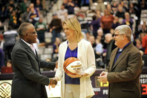 UAlbany women's coach Katie Abrahamson-Henderson, center, is honored for her 200th career victory at halftime in the men's basketball game against Vermont on Saturday, Feb. 28, 2015, at UAlbany in Albany, N.Y. Joining her are UAlbany president Robert J. Jones, left, and Charlie Voelker, associate athletic director. (Cindy Schultz / Times Union) Photo: Cindy Schultz / 00030743A