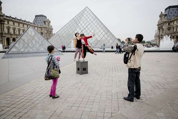 FILE - Chinese tourists pose for a photo in front of the Louvre in Paris, Sept. 4, 2014. Europe's leading currency has plunged closer and closer to parity with the dollar, to the delight or dread of prospective tourists and business travelers. (Marlene Awaad/The New York Times)