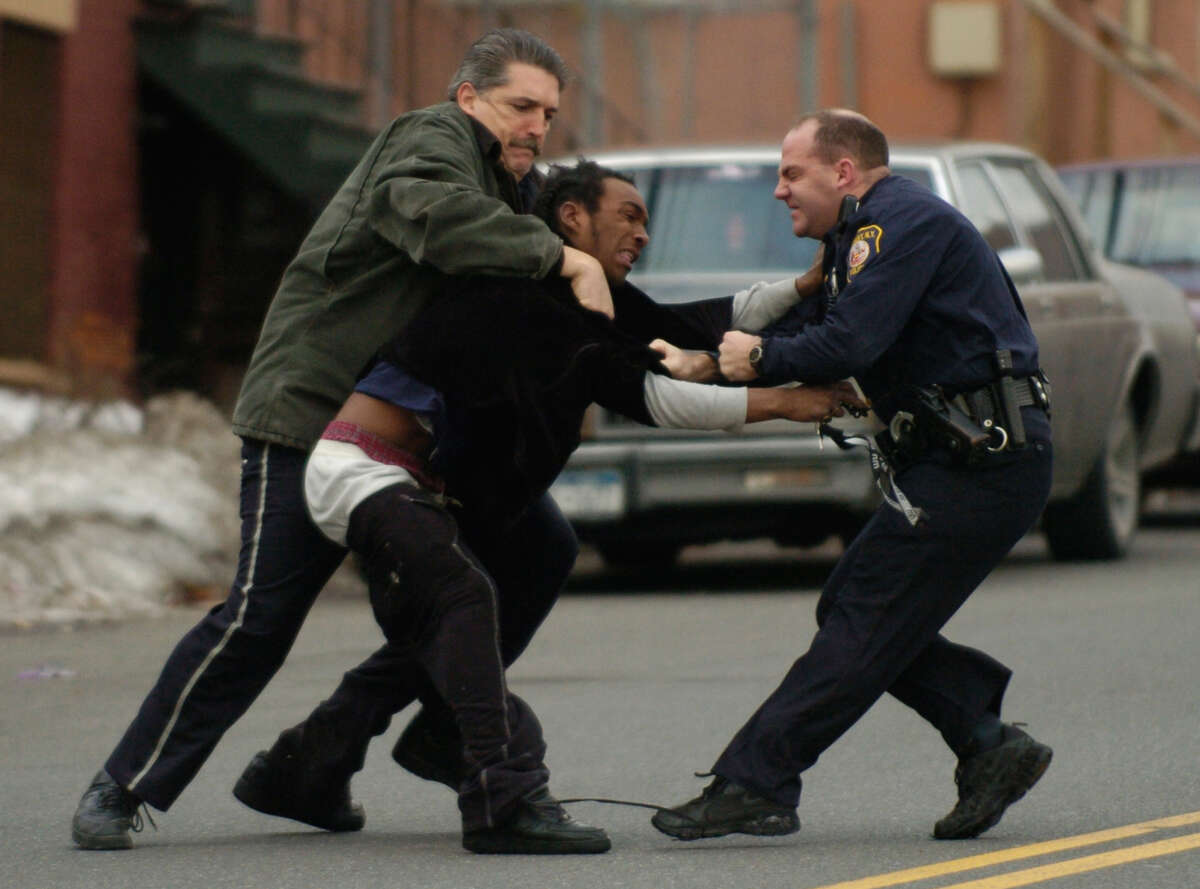 Albany Police officer Robert E. Schunk, right, and Hal Warner, left, take a man into custody in 2003. (Skip Dickstein/Times Union archive)