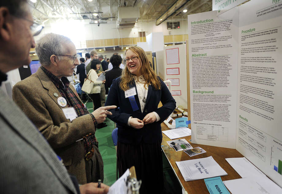 Sarah Mack, a junior at Christian Heritage School in Trumbull, discusses her project with judges Jack Solomon, left, and Henry Link during finals judging of the 67th annual Science and Engineering Fair at Quinnipiac University in Hamden, Conn. on Thursday, March 12, 2015. Mack studied the production of biodiesel from laboratory grown algae. Photo: Brian A. Pounds / Connecticut Post
