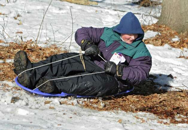 Lucas Salmon, 11, of Niskayuna hits a grassy patch and stops abrupty while sledding on hill near Central Park on Thursday, March 12, 2015 in Schenectady, N.Y.  (Lori Van Buren / Times Union) Photo: Lori Van Buren / 00031003A