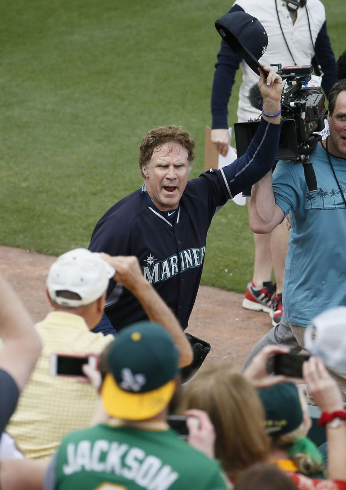 Actor Will Ferrell acknowledges the fans after playing second base for the Seattle Mariners during the second inning of a spring training baseball game against the Oakland Atletics, Thursday, March 12, 2015, in Mesa, Ariz. The comedian plans to play every position while making appearances at five Arizona spring training games on Thursday. (AP Photo/Matt York)