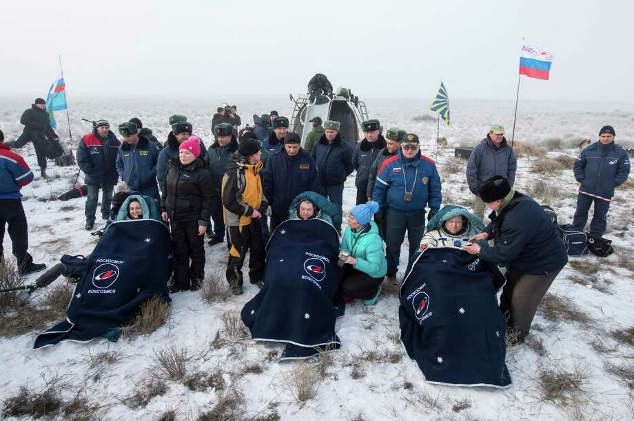 Russian Cosmonauts Elena Serova, left, Alexander Samokutyaev of Roscosmos, center, and NASA Astronaut Barry Wilmore of NASA sit in chairs outside the Soyuz TMA-14M spacecraft just minutes after they landed in a remote area near the town of Zhezkazgan, Kazakhstan on Thursday, March 12, 2015. NASA Astronaut Wilmore, Russian Cosmonauts Samokutyaev and Serova are returning after almost six months onboard the International Space Station. (AP Photo/NASA, Bill Ingalls) Photo: Bill Ingalls, HOPD / NASA