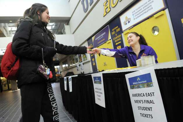 UAlbany cheer team member Madison Corbeil, right, hands America East Championship tickets to university senior student Rebecca Ringer on Thursday March 12, 2015 in Albany, N.Y. UAlbany students with identification where eligible for one ticket to both the women's and men's games. (Michael P. Farrell/Times Union) Photo: Michael P. Farrell / 00030997A