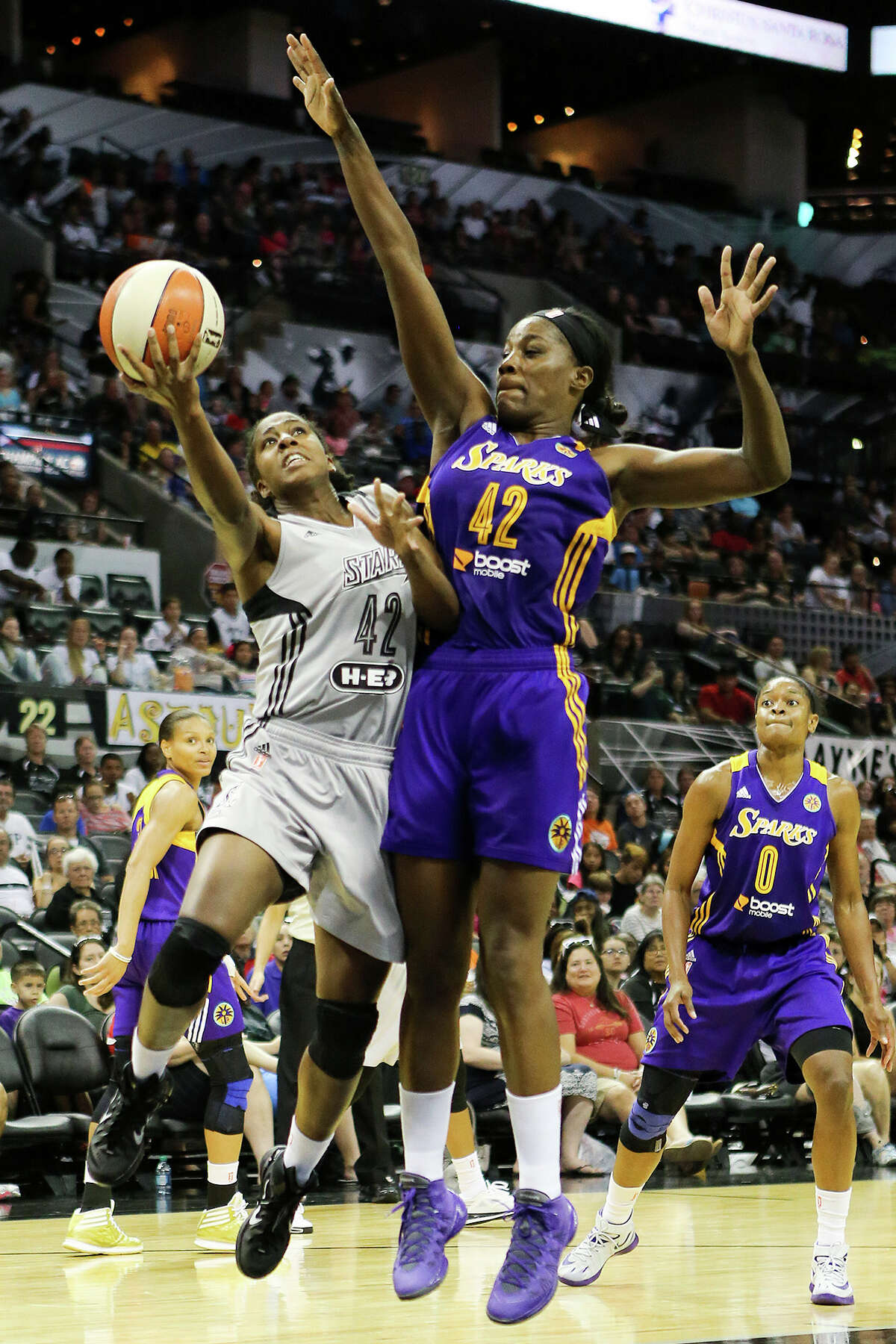 Shenise Johnson of the Stars (left) tries to get a shot past Jantel Lavender of the Los Angeles Sparks during the second half of their game at the AT&T Center on Aug. 10, 2014. The Stars beat the Sparks 82-76