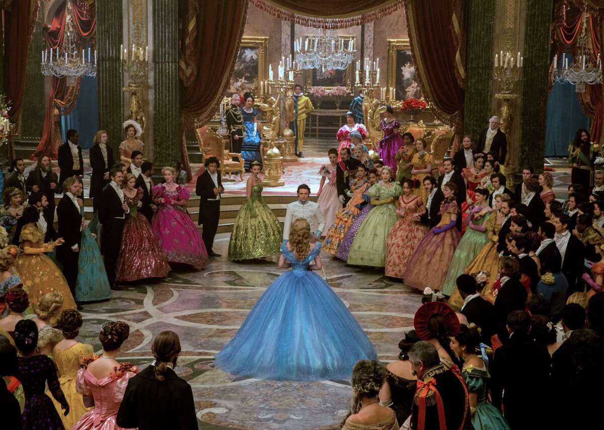 This image released by Disney shows Lily James as Cinderella, center, and Richard Madden as the Prince, background center, in Disney's live-action feature inspired by the classic fairy tale,