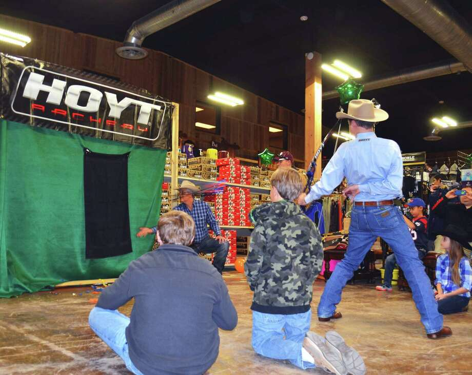 Exhibition archer Frank Addington fires three arrows from a bow held behind his back to hit three baby aspirins tossed into the air during a demonstration of extreme archery accuracy at Wheeler's Feed and Outfitter's in Boerne. Photo: Ralph Winingham /For The Express-News