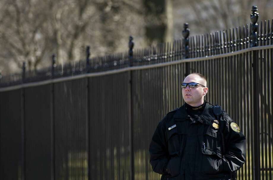 An uniformed US Secret Service officer (C) patrols Pennsylvania Avenue in front of the White House in Washington, DC, March 12, 2015 as a man takes a selfie. The US Secret Service is investigating claims that some of its agents crashed a car into White House security barriers after a night out, The Washington Post reported March 11. The Secret Service was not immediately available to confirm the report, but spokesman Brian Leary told the Post that the probe would be conducted by the Department of Homeland Security's inspector general.     AFP PHOTO/JIM WATSONJIM WATSON/AFP/Getty Images Photo: JIM WATSON, Staff / AFP / Getty Images / AFP ImageForum