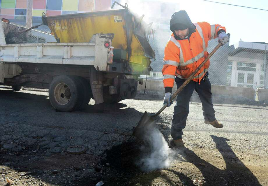 Bridgeport Public Works employee Phillip Jaiman, of Stratford, repairs potholes Thursday, Mar. 12, 2015 on Prospect Street in Bridgeport. The recent thaw has put the city on pothole patrol, working to fix the damage to roads left behind by winter. Photo: Autumn Driscoll / Connecticut Post