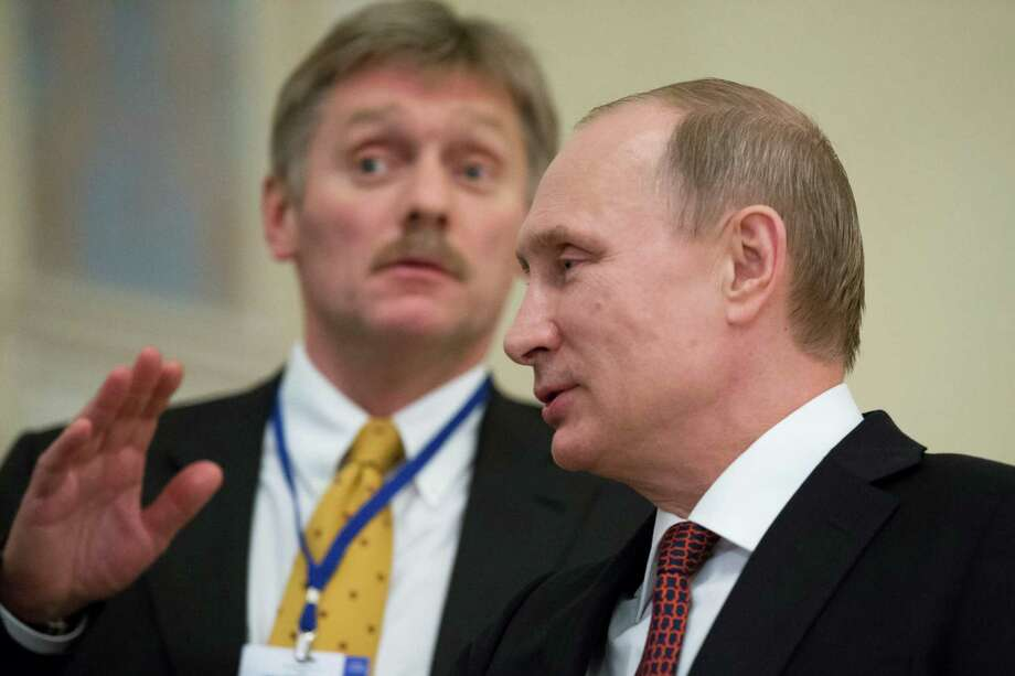 "In this photo taken on Thursday, Feb.  12, 2015, Russian President Vladimir Putin,  right, speaks to a journalist as his press secretory  Dmitry Peskov tries to stop questions after the peace talks in Minsk, Belarus, Thursday, Feb. 12, 2015.  Peskov told The Associated Press that Putin's ""health is really perfect,"" dismissing media speculation that the president could be unwell.  (AP Photo/Alexander Zemlianichenko) Photo: Alexander Zemlianichenko, STF / AP"