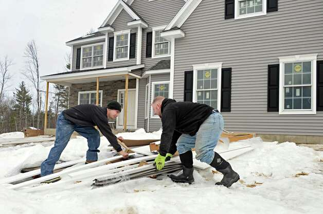 Barbera Homes employees Jimmy Warlikowski, left, and Rich Menendez sort through building materials outside a new home on Barn Owl Place in the Stone Crest development Tuesday March 10, 2015 in Halfmoon, NY.  (John Carl D'Annibale / Times Union) Photo: John Carl D'Annibale / 00030924A