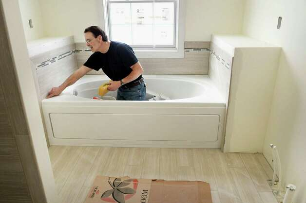 Tiler Doug Rivenburg gouts a bathtub inside a new home under construction on Barn Owl Place in the Stone Crest development Tuesday March 10, 2015 in Halfmoon, NY.  (John Carl D'Annibale / Times Union) Photo: John Carl D'Annibale / 00030924A