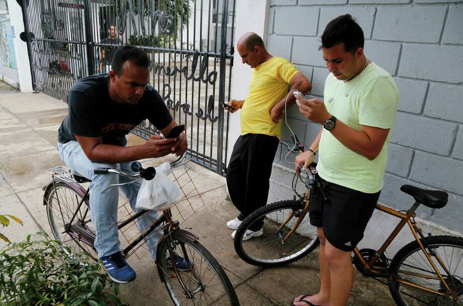 People stand in front of a center run by famed artist Kcho, to use the free Wi-Fi network, in Havana, Cuba, Wednesday, March 11, 2015. Dozens of youths from around the city flock daily to the center. Kcho's spokeswoman said state telecom Etecsa approved the move in a small but unprecedented loosening of Cuba's strict Internet regulations. (AP Photo/Desmond Boylan) Photo: Desmond Boylan, STR / Associated Press / AP