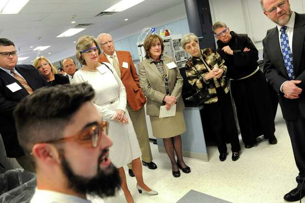 John Gilbert, 21, in foreground, shows trustees the scanning electron microscope during a tour of Stewart's Advanced Instrumentation and Technology Center, made possible through an endowment from William Dake, center, and his wife and trustee Susan Dake, to his left, on Thursday, March 12, 2015, at Siena College in Loudonville, N.Y. At right is Allan Weatherwax, dean of the School of Science, and to his left is Brother F. Edward Coughlin, college president. (Cindy Schultz / Times Union) Photo: Cindy Schultz / 00030961A