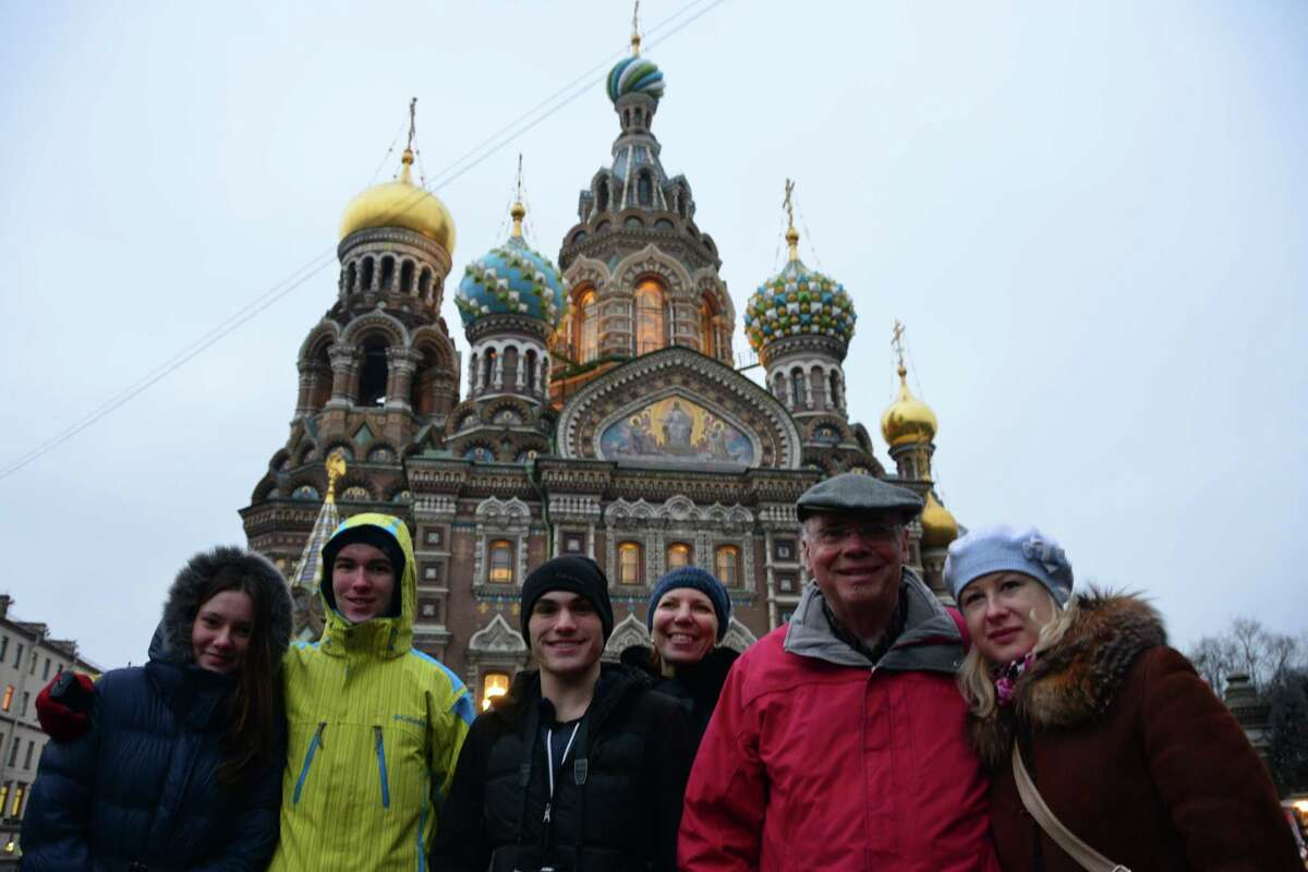 Isaac Smith (second from left), a homeschooler from Clifton Park; Tarek Atallah-Benson, a St. Rose student from Albany; and chaperone/former news anchor Jack Aernecke, with their Russian hosts outside a cathedral in St. Petersburg.