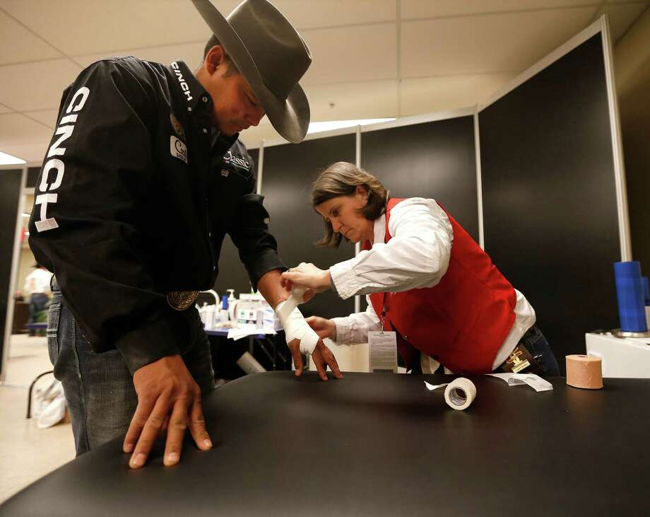 Michelle Leget, an athletic trainer, tapes Erich Rogers' wrist during the Houston Livestock Show and Rodeo at NRG Park, Tuesday, March 10, 2015, in Houston. ( Karen Warren / Houston Chronicle  ) Photo: Karen Warren, Staff / © 2015 Houston Chronicle