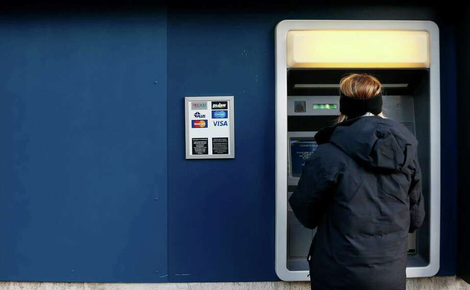 FILE - In this Jan. 5, 2013 file photo, a woman uses an ATM machine in downtown Pittsburgh. The Federal Reserve reports on household wealth for the October-December quarter of 2014 on Thursday, March 12, 2015. (AP Photo/Gene J. Puskar, File) Photo: Gene J. Puskar, STF / AP