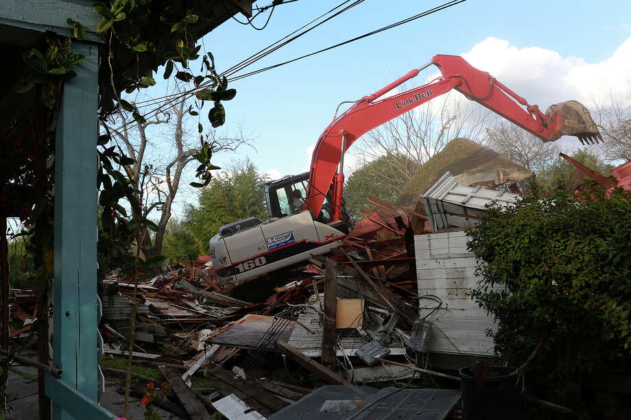 Eric Castillo with Jarvis Moore Inc. uses an excavator Thursday to demolish the home owned by Syngman Stevens at 619 Nolan St. Photo: Lisa Krantz /San Antonio Express-News / San Antonio Express-News
