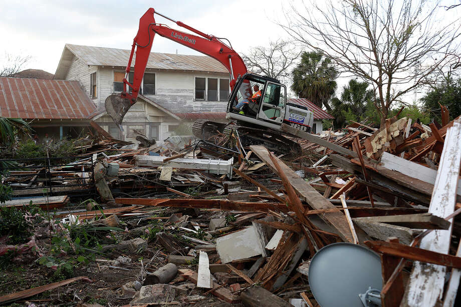 Eric Castillo with Jarvis Moore Inc. works Thursday to finish the demolition of two homes owned by Syngman Stevens at 619 and 621 Nolan St. Photo: Lisa Krantz /San Antonio Express-News / San Antonio Express-News