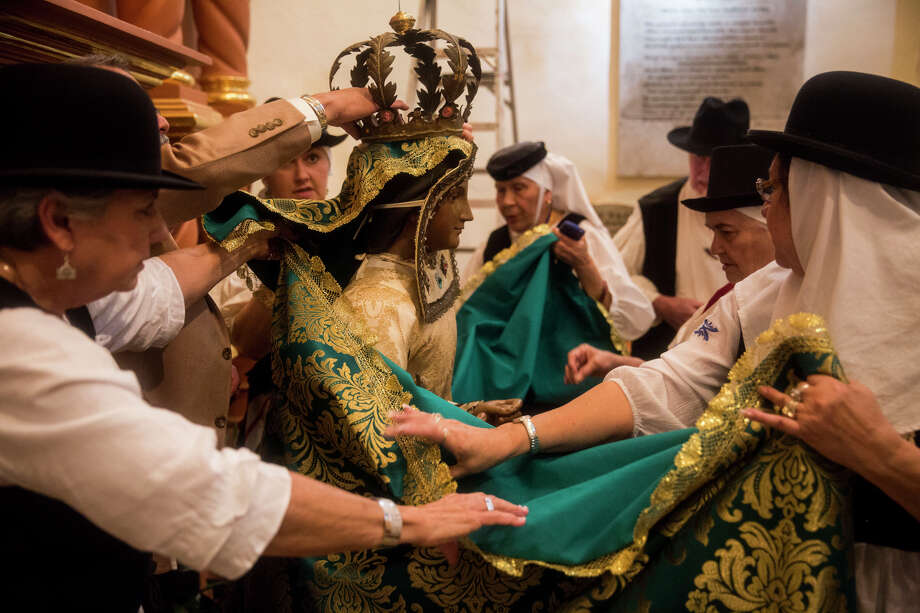 Local descendants of the Canary Islanders dress the historic Our Lady of Candelaria statue in new clothing from the Canary Islands at the San Fernando Cathedral in San Antonio, TX on Thursday, March 12, 2015. Photo: Carolyn Van Houten, Staff / San Antonio Express-News / 2015 San Antonio Express-News