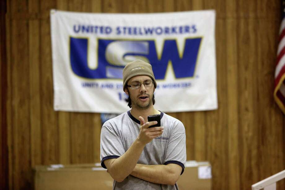 Joshua Lege, union steward/alternate committee member, reads a press release to U.S. Steelworkers union members of the tentative agreement on a four year contract with Shell Oil Company at the U.S. Steel Local 13-227 Thursday, March 12, 2015, in Pasadena, Texas. ( Gary Coronado / Houston Chronicle ) Photo: Gary Coronado, Staff / © 2015 Houston Chronicle
