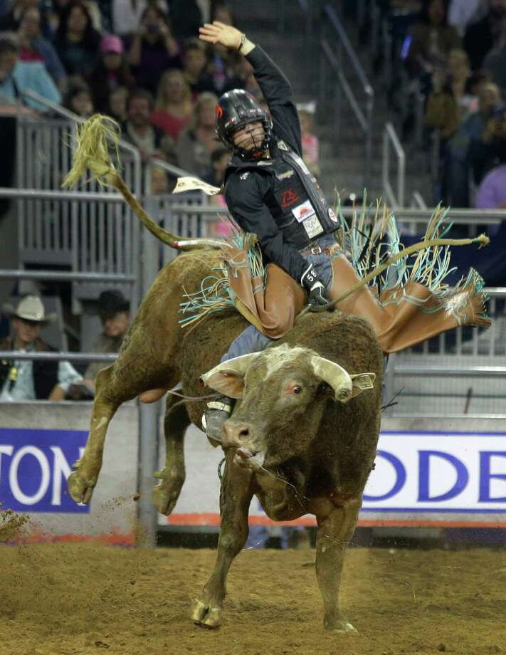 Sage Kimzey sits tall in the saddle during the bull-riding competition Thursday at NRG Stadium. He's in second place after the first of three rounds. Photo: Melissa Phillip, Staff / © 2014  Houston Chronicle