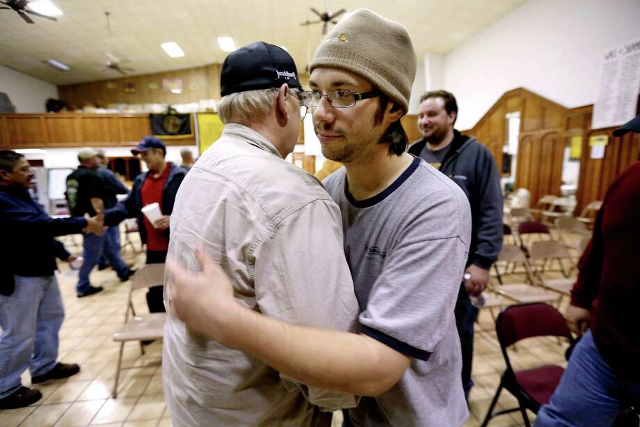 Rick Brummett (left) gives union steward Joshua Lege a hug after Lege read a news release to U.S. Steelworkers of the tentative agreement on a four-year contract with Shell Oil. Photo: Gary Coronado /Houston Chronicle / © 2015 Houston Chronicle