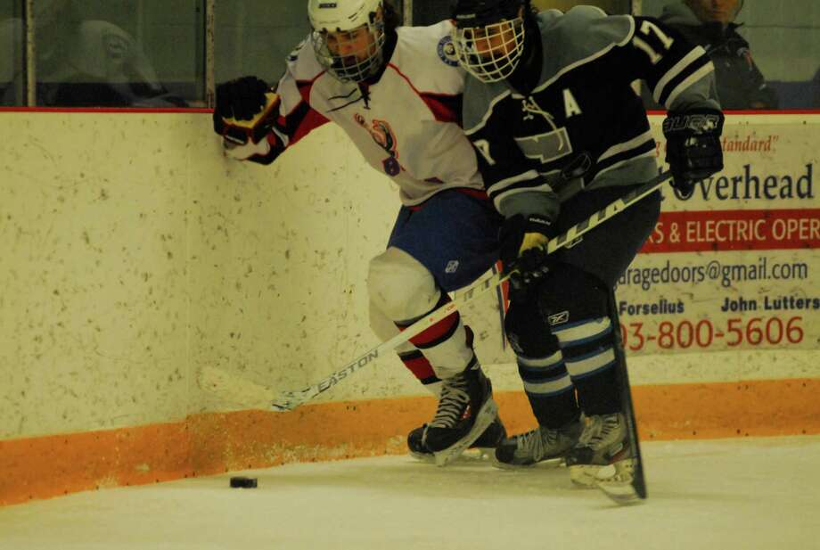 Staples-Weston-Shelton's RJ Gupta, right, battles for the puck with E.O. Smith-Tolland's Michael Lennon during their Division III quarterfinal on Thursday. The Bucks ended the Wreckers' season with a 5-0 win. Photo: Ryan Lacey/Staff / Westport News Contributed
