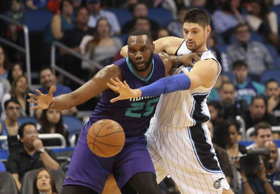 Charlotte Hornets' Al Jefferson and Orlando Magic center Nikola Vucevic fight for a loose ball during first half action on Sunday, March 1, 2015, at the Amway Center in Orlando, Fla. (Tom Benitez/Orlando Sentinel/TNS) Photo: Tom Benitez, MBR / Orlando Sentinel